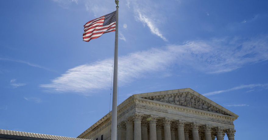 the supreme court under a blue sky, flag waving