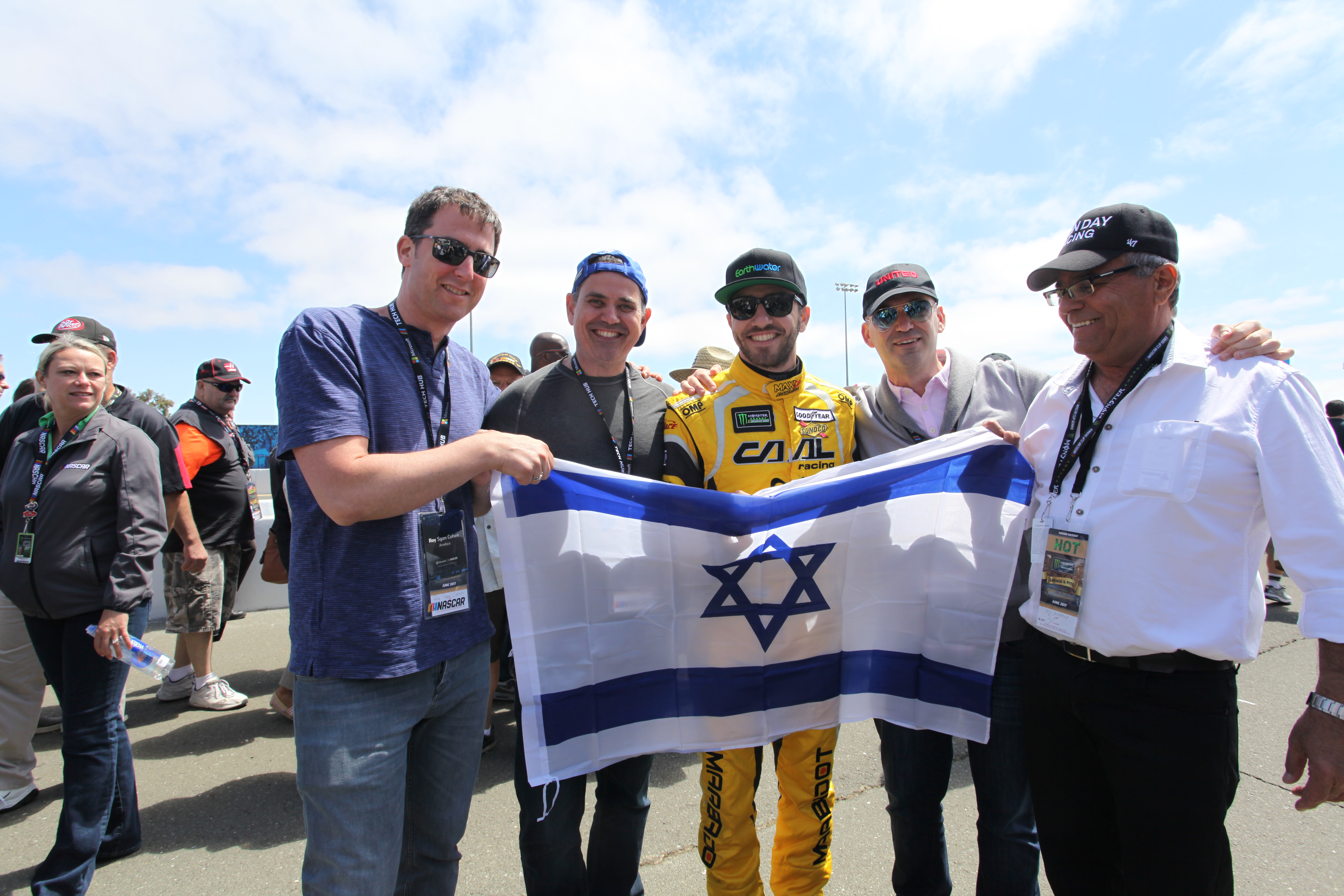 Israeli NASCAR driver Alon Day (center) with (from left) Roy Cohen, Avishai Sharlin, Dan Hod and Avi Day (Alon's dad) at the Sonoma Raceway unfurling an Israeli flag (Photo/Max A. Cherney)