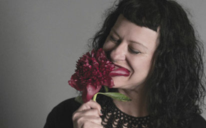 gottlieb has tattoos and is dressed all in black as she sniffs a red flower