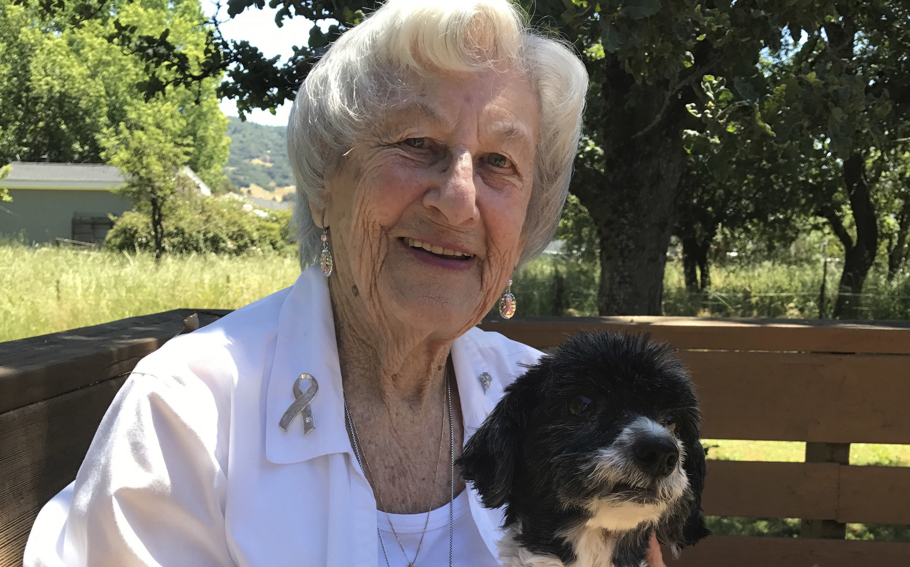 and old woman sits smiling on a park bench with a small black and white dog on her lap