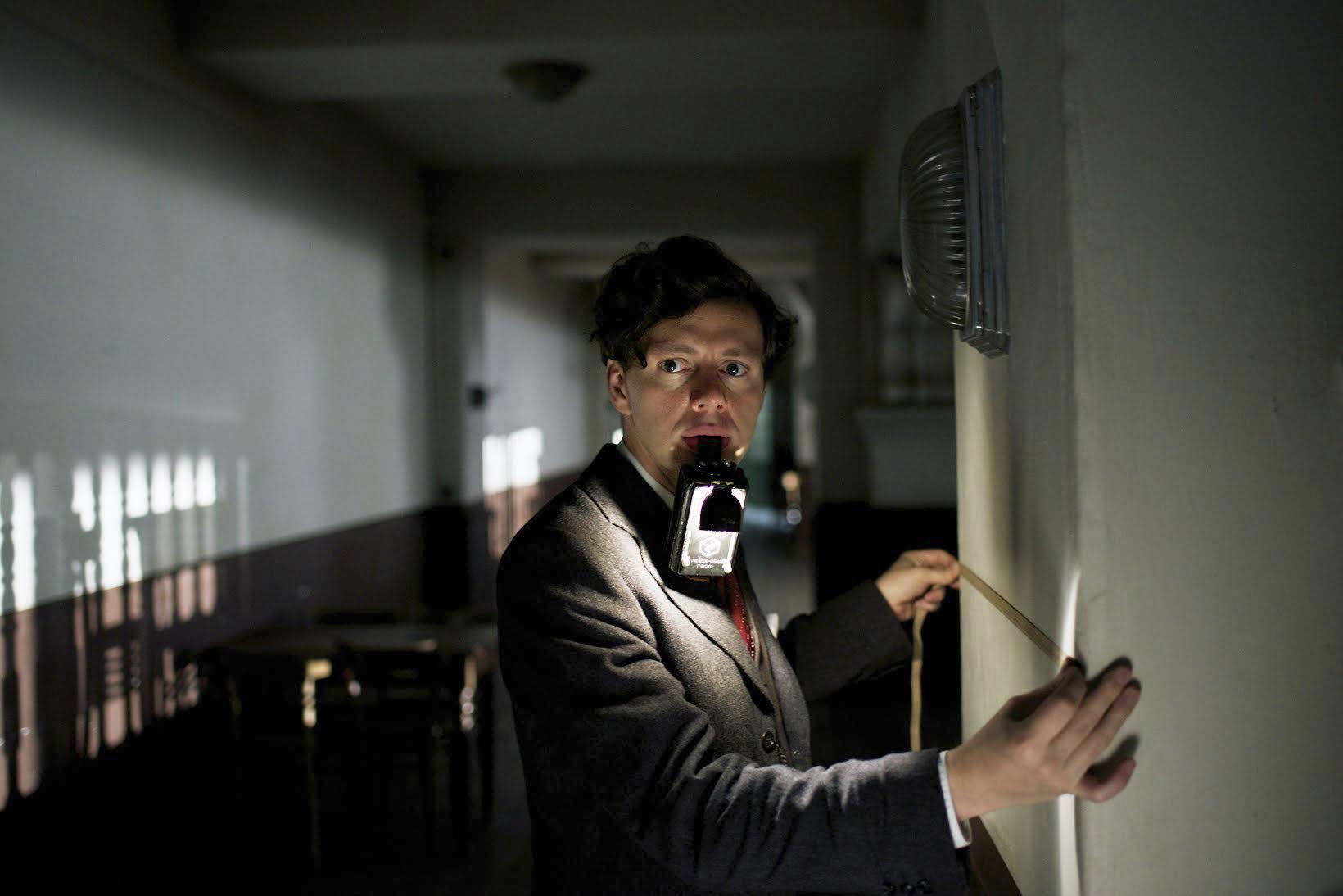 a suspicious looking man in a dark hallway