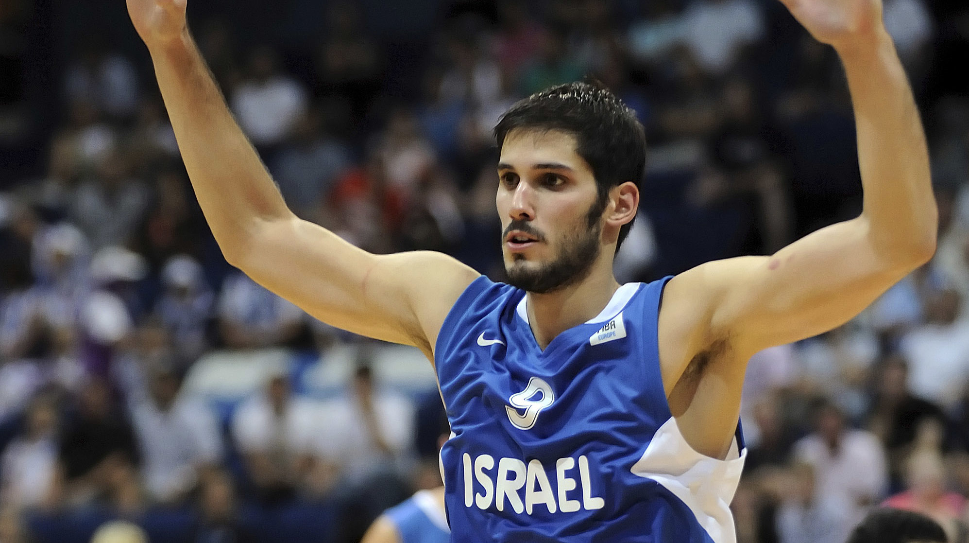 casspi raises his hands on the court, wearing an israel jersey