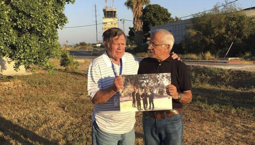 two older men stand together holding a photo of them in 1973