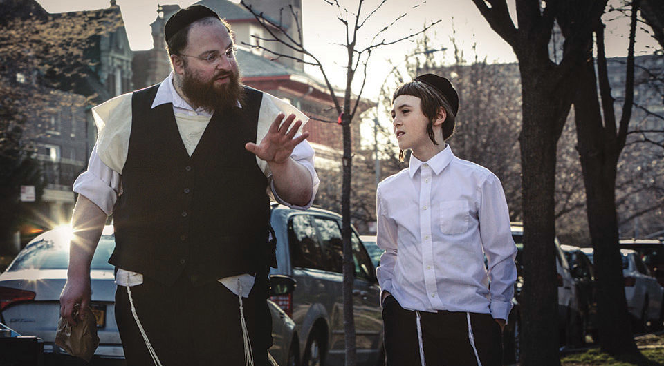 a man (Menashe) and boy walking down the street together, both in traditional hasidic garb