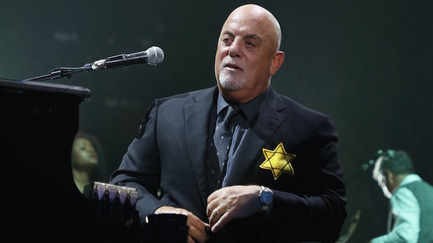 Billy Joel wearing a yellow Star of David during the encore of a show at Madison Square Garden in New York City, Aug. 21, 2017 (Photo/JTA-Myrna M. Suarez-Getty Images)