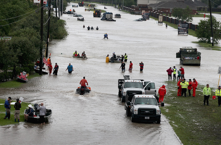 Houston residents and rescuers make their way out of a flooded neighborhood after it was inundated with rain following Hurricane Harvey, Aug. 29, 2017. (Photo/JTA-Scott Olson-Getty Images)