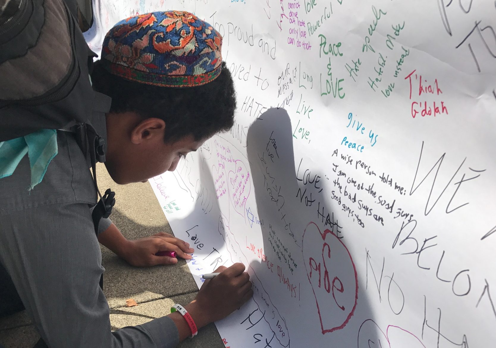 Eric Getreuer, 16, writing butcher paper that was put up over the anti-Semitic graffiti defacing Temple Israel (Photo/Sue Fishkoff)