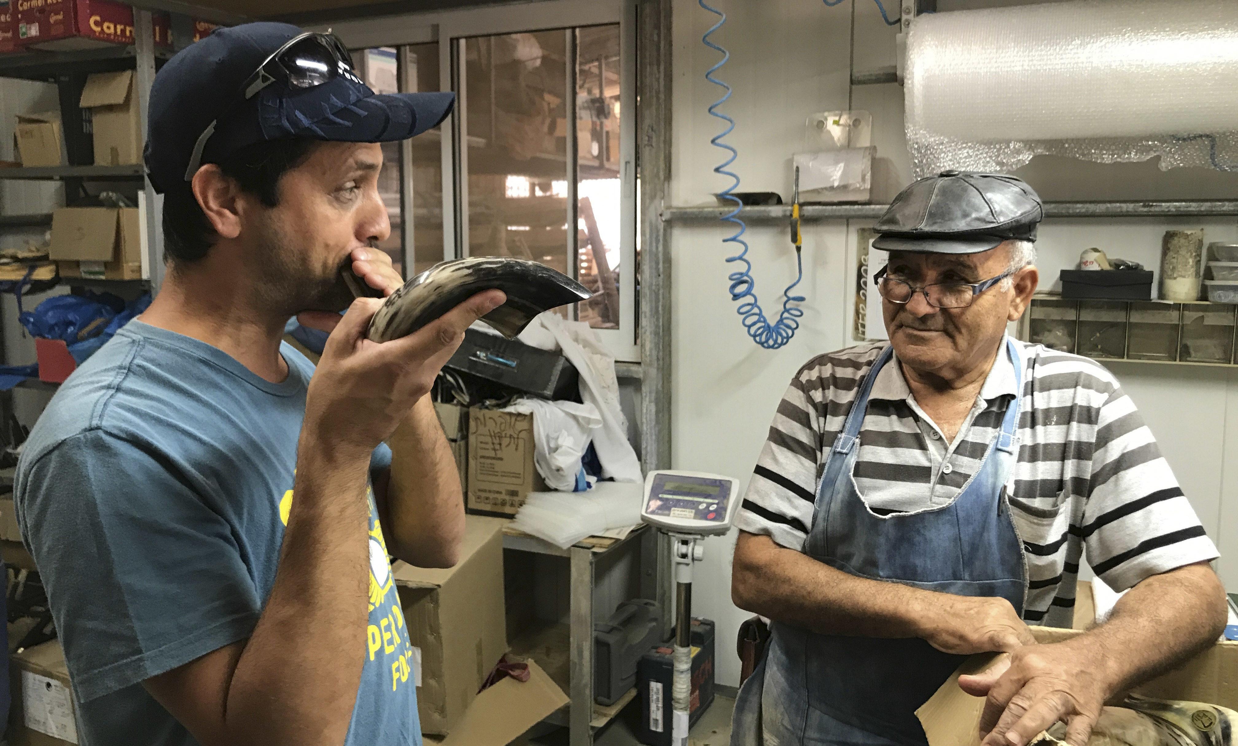Dror Yoggev blowing a shofar while Shimon Keinan watches at his Kol Shofar factory in Givat Yoav, Golan Heights, Sept. 6, 2017 (Photo/JTA-Andrew Tobin)