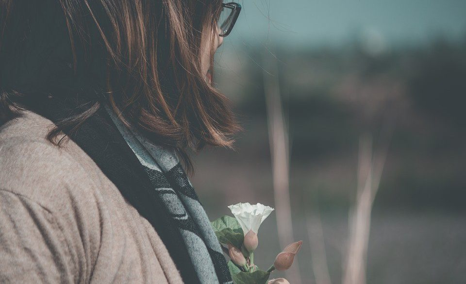 a melancholy photo of a women looking away holding a flower