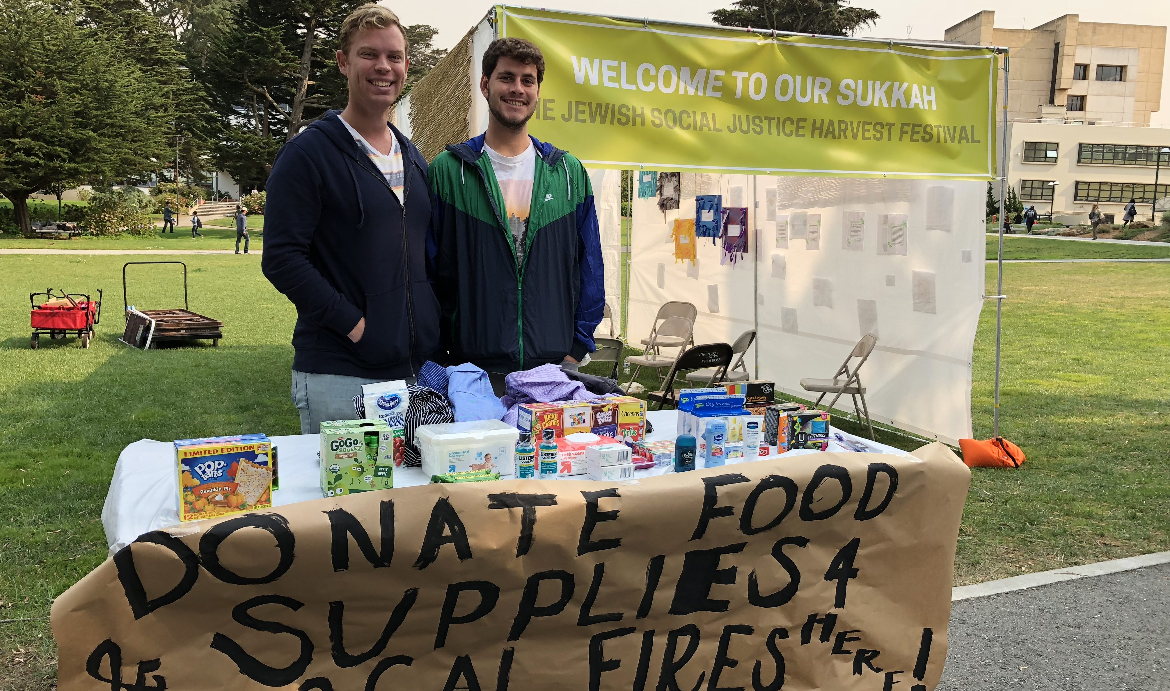 SF Hillel students Benjamin Gaster (left) and Jake Scheinberg collecting donations in front of their campus sukkah. (Photo/Courtesy SF Hillel)