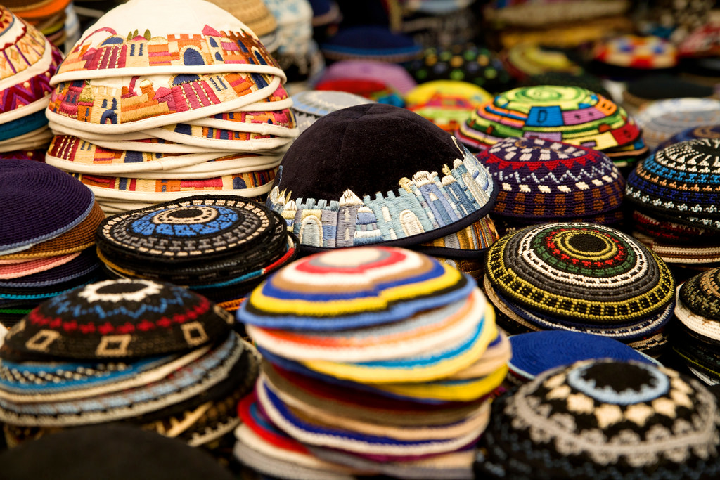 stacks of kippot in all sizes and colors at a market in Israel