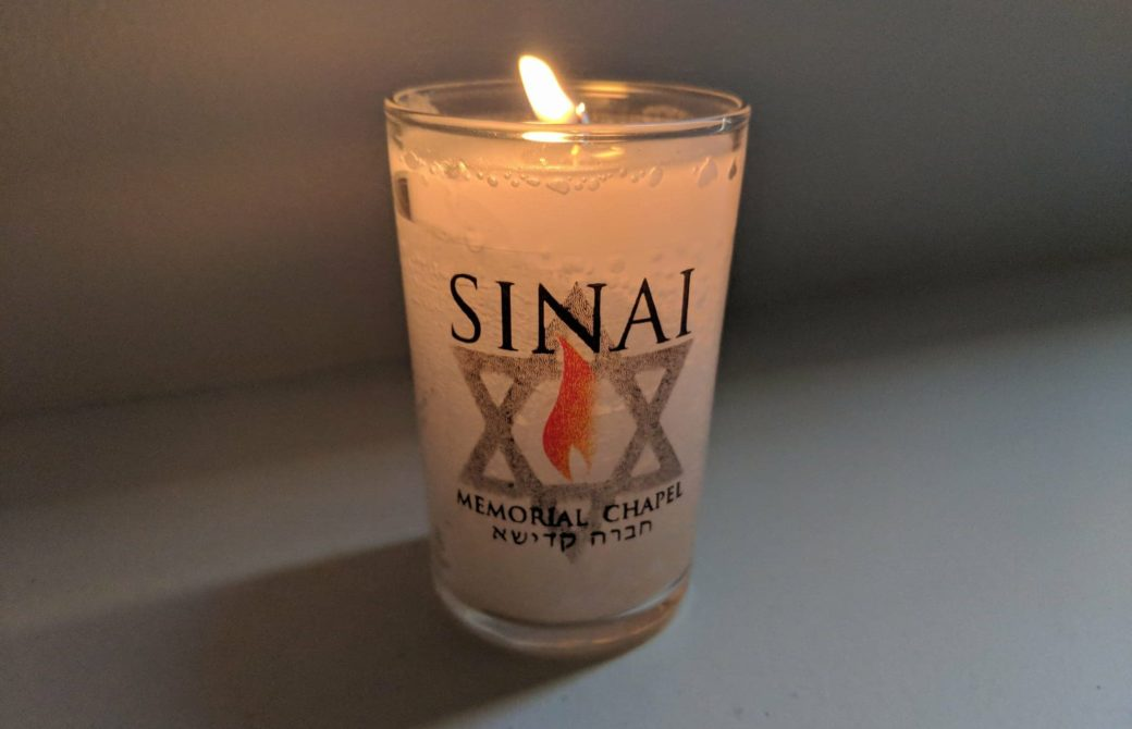 a lit memorial candle with a Sinai Memorial Chapel logo on it
