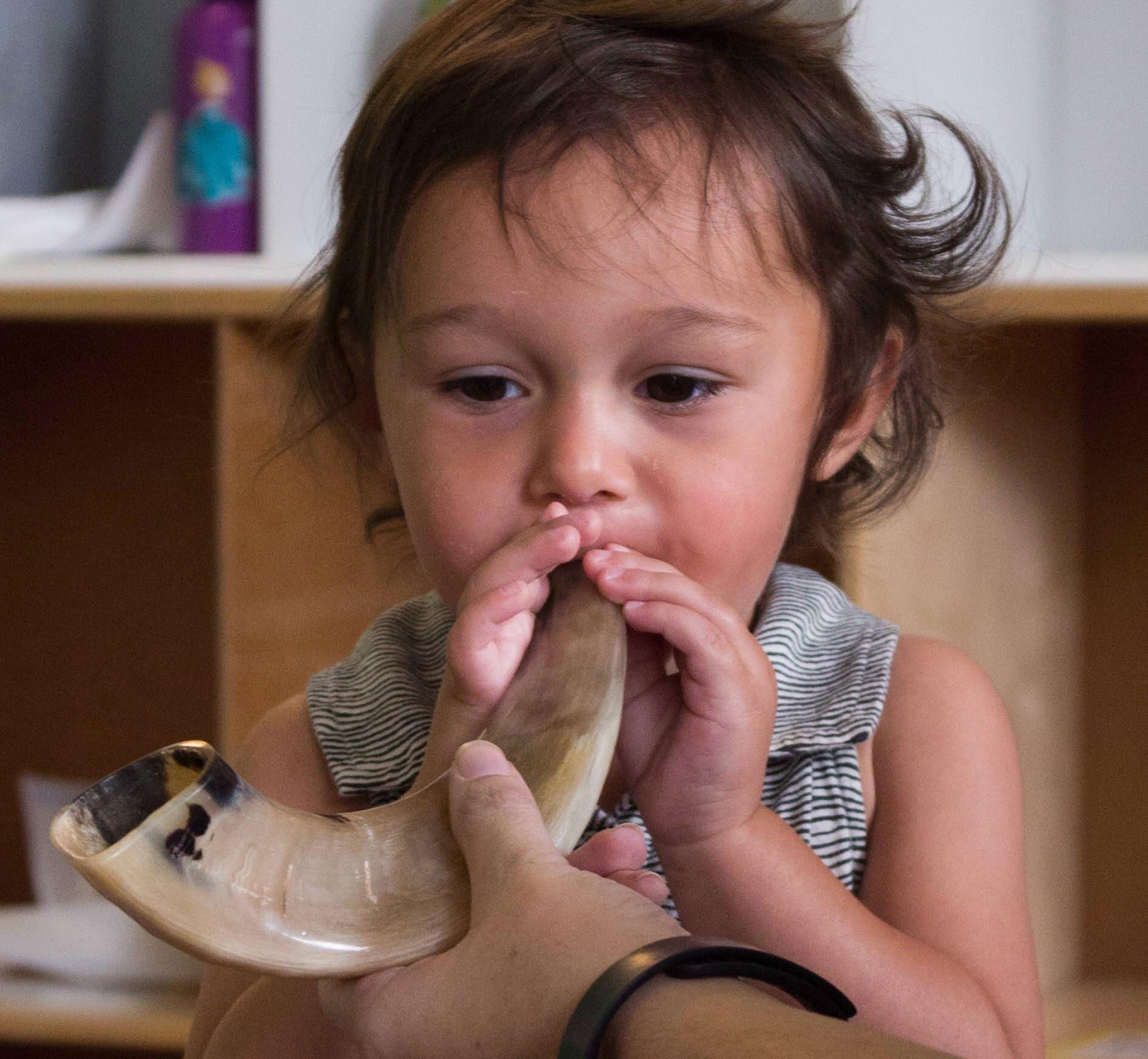 Shoshana Edelstein blows a shofar with help from Emma Schnur. Shoshana attends Gan Avraham Preschool at Temple Beth Abraham in Oakland, a participant in the Federation's Jewish Resource Specialists program. (Photo/Rachel Regan)