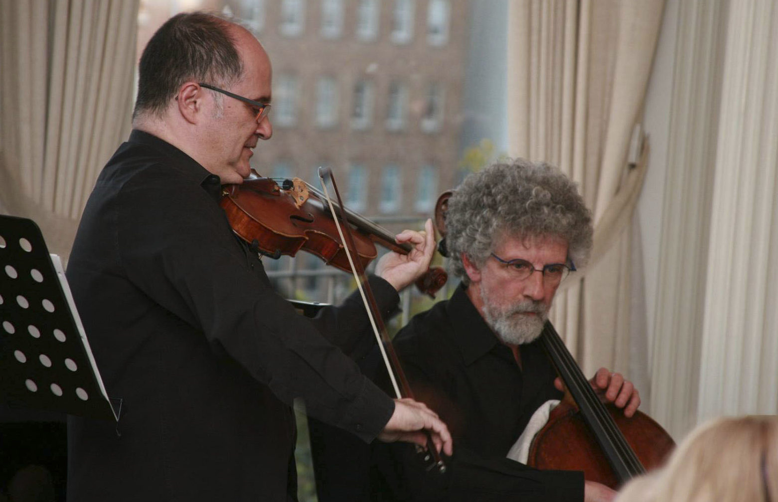 At the German Consulate in S.F., violinist Mikhail Shmidt and cellist Water Gray of the Seattle Symphony perform excerpts from the upcoming Music of Remembrance concert. (Photo/Gabriele Lange)