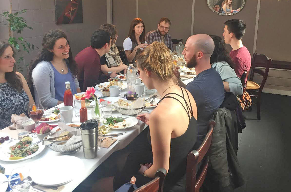 Purim meal hosted by Robyn Monroe in 2017 (fourth from left, in striped scarf)
