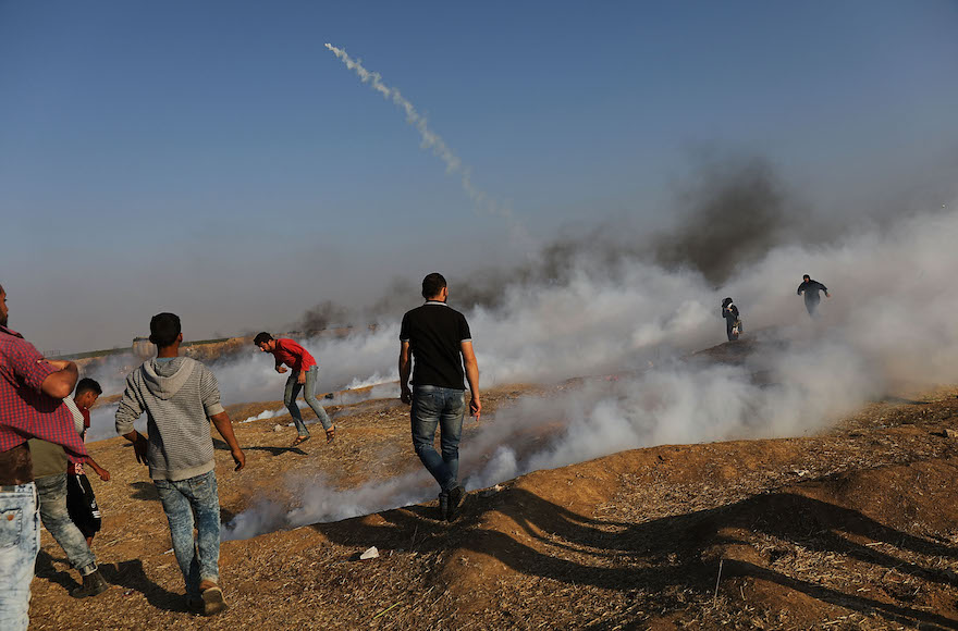 People running from tear gas at the border fence with Israel in Gaza City, May 15, 2018 (Photo/JTA-Spencer Platt-Getty Images)
