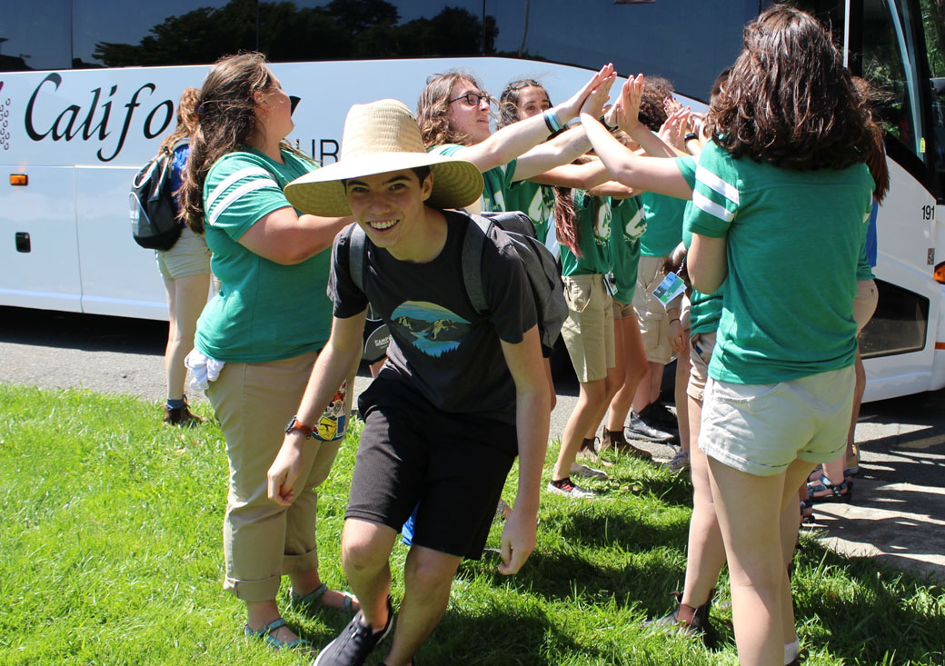 """Campers from the San Rafael/Santa Rosa bus arrive at California State University Maritime Academy to the tune of """"Shalom Aleichem,"""" sung by the counselors in training. (Photo/Olivia Smith)"""