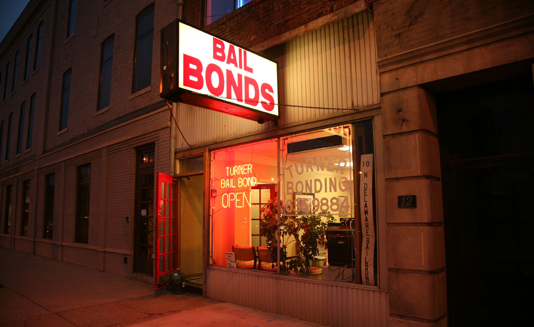 bail bonds storefront lit in eerie red neon