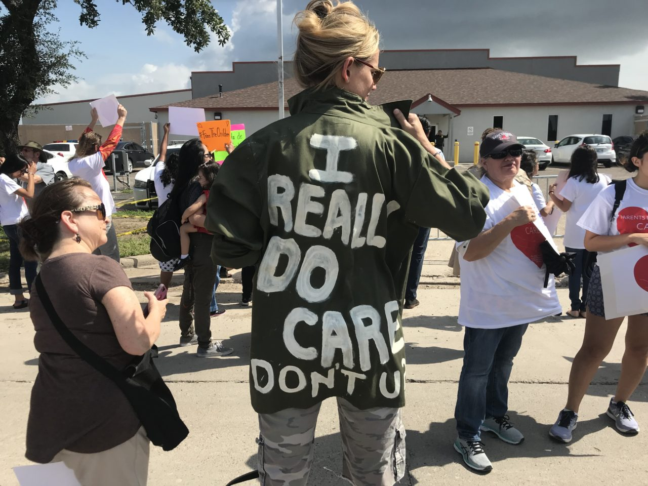 "A woman with her back to the camera; the back of her jacket reads: ""I really do care, don't you?"""