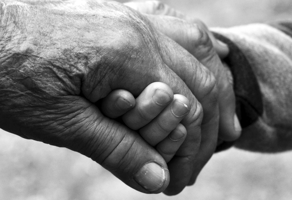 black and white image of two senior hands holding on to each other
