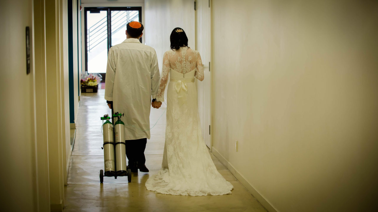 Nguyen and Koller walk down a hallway in their wedding outfits, holding hands — he is toting her oxygen tank behind himself