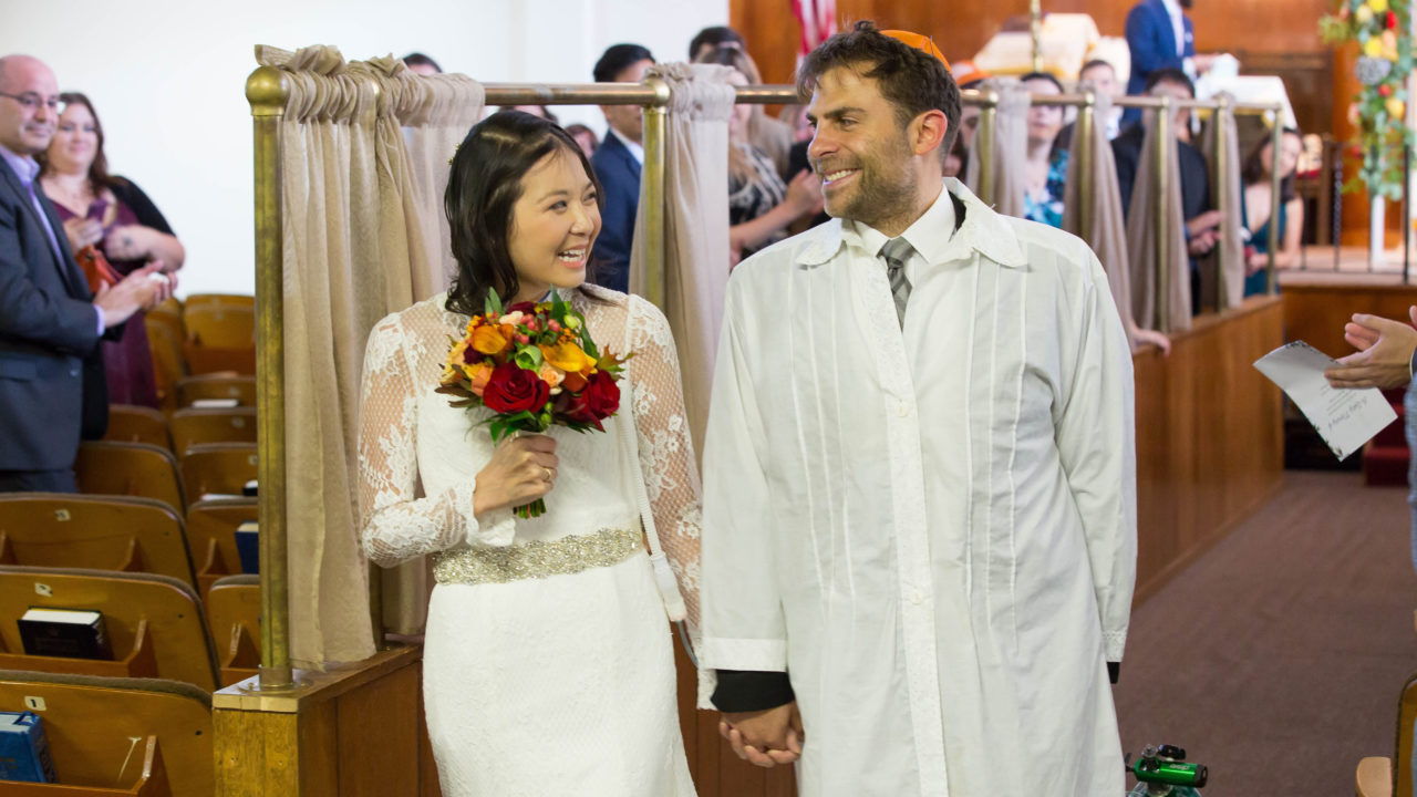 Vy Nguyen and Andrew Koller walk down the aisle at their wedding at Congregation Chevra Thilim in San Francisco on Oct. 7, 2018. (Photo/David Nguyen)