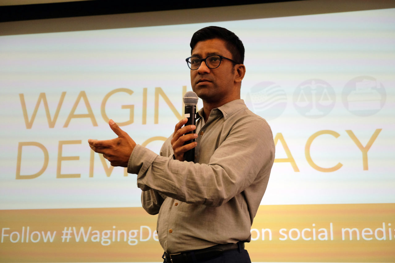 "Huq speaks holding a mic in front of a sign that says ""Waging Democracy"""