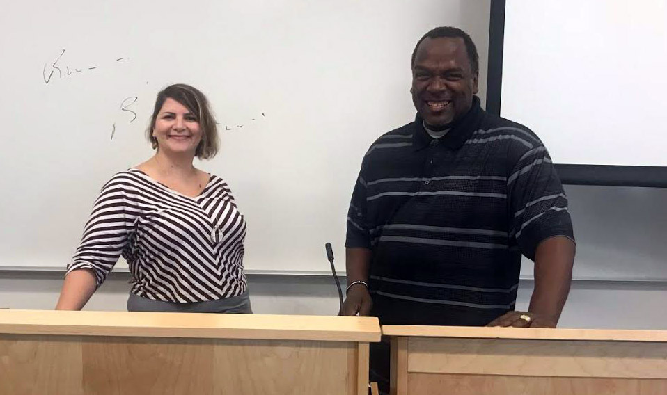 the two stand smiling in a classroom