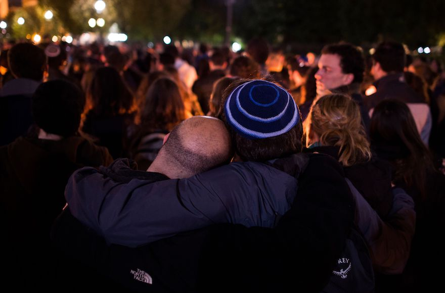 people in kippot embrace during a memorial event
