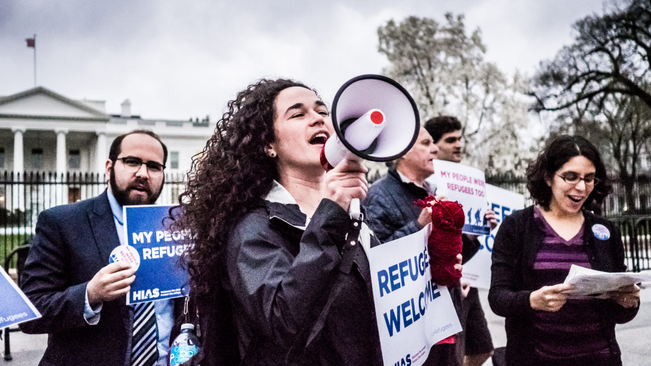 """a woman with a """"refugees welcome"""" sign shouts into a megaphone"""