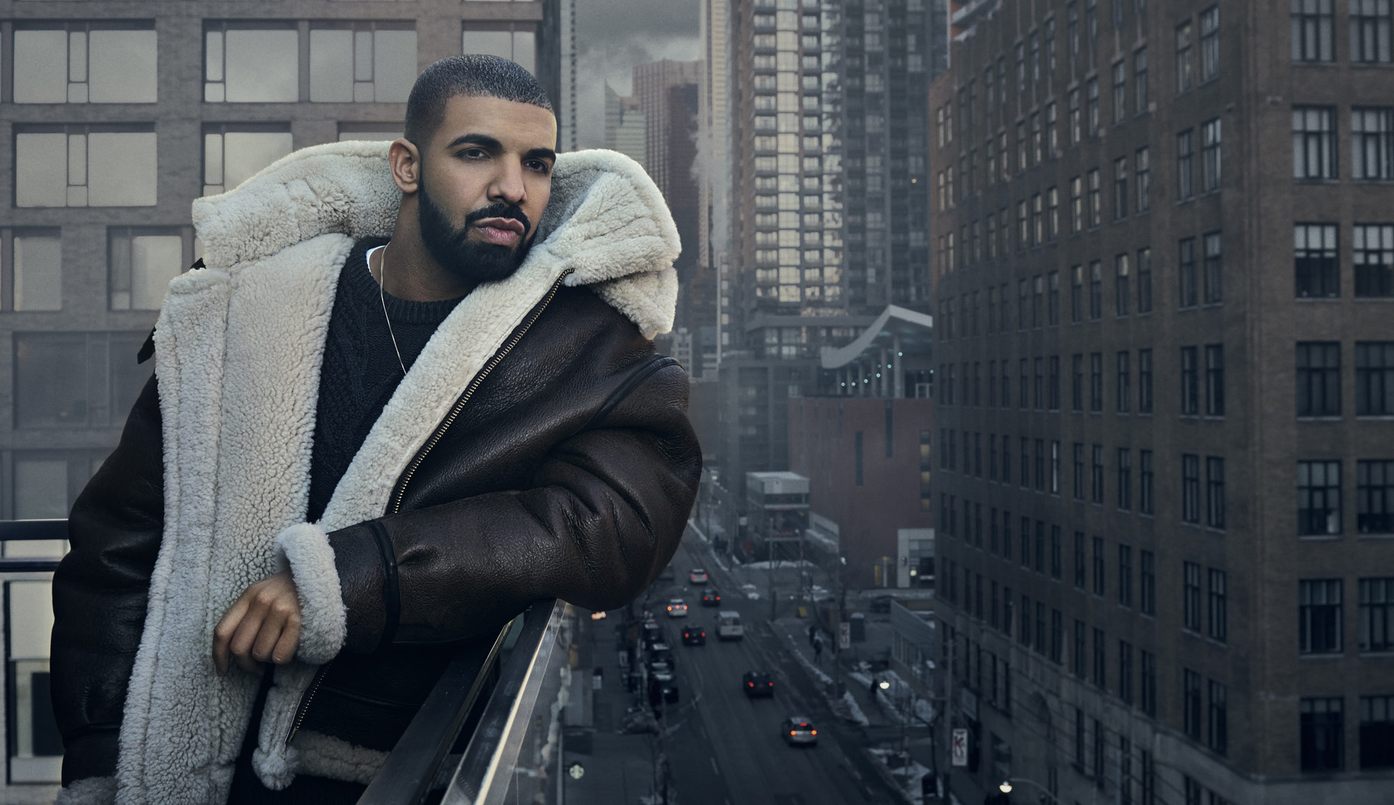 Drake wearing an oversized leather, shearling-lined coat on a balcony overlooking a busy city street