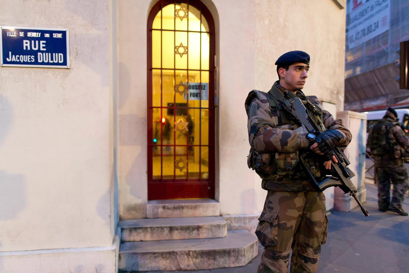 an armed officer stands outside a synagogue doorway
