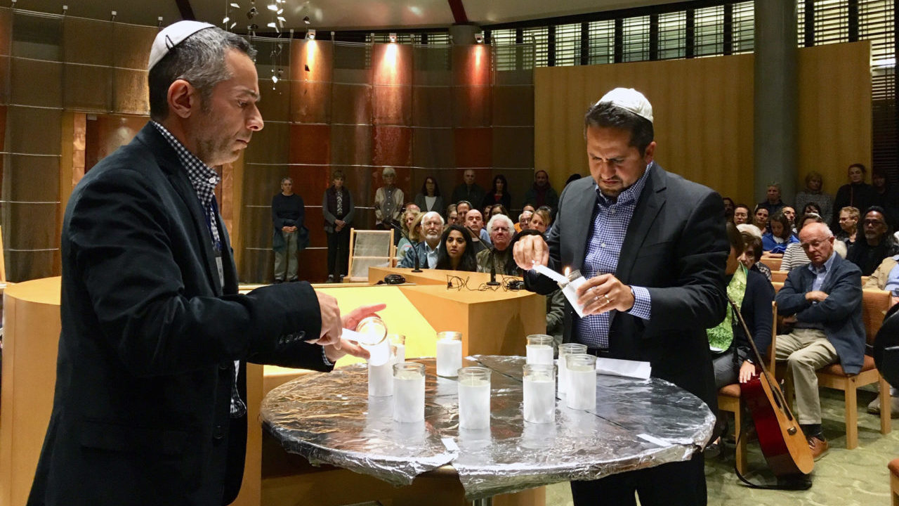 two men light candles in the middle of a packed sanctuary