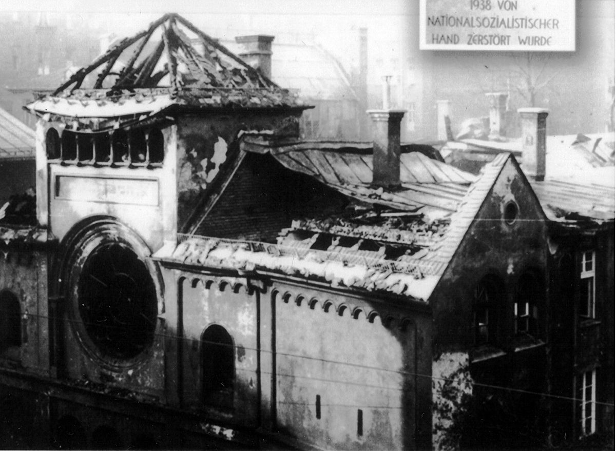 a ruined synagogue, roof caved in and windows smashed, seen from above