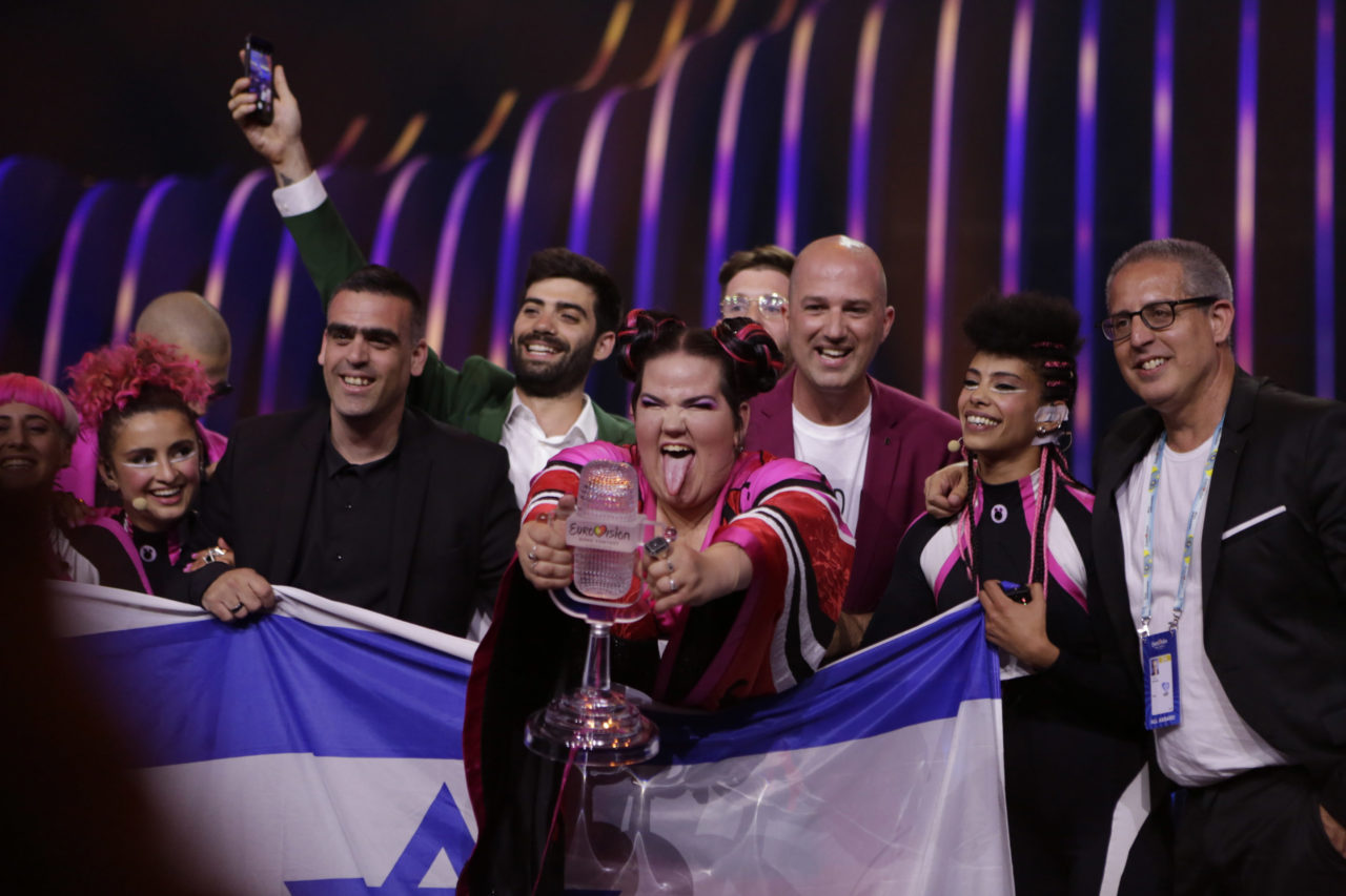 Netta sticks her tongue out, holding trophy and israeli flag, surrounded by supporters