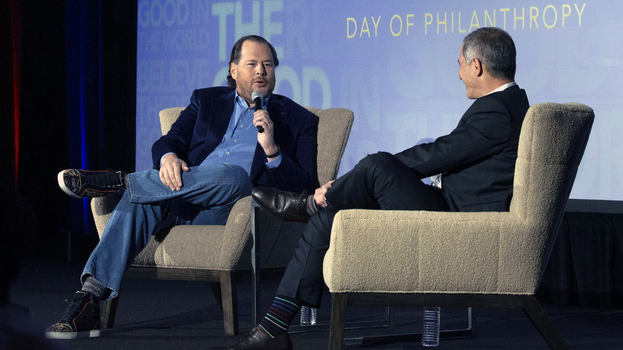 Benioff sits on stage with a mic across from another man