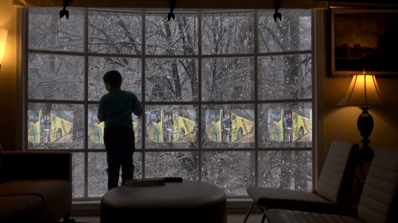 the silhouette of a person looking out a window. there is snow falling outside.