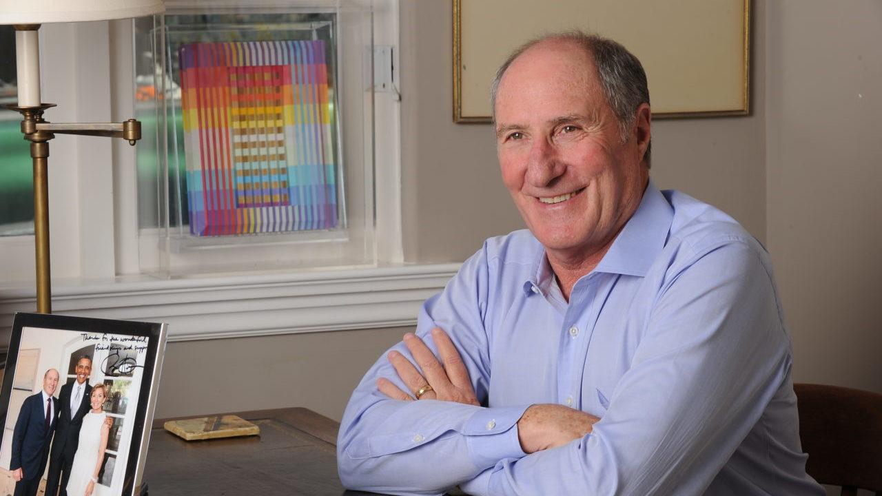 Goldman, older bald man, sits at a desk