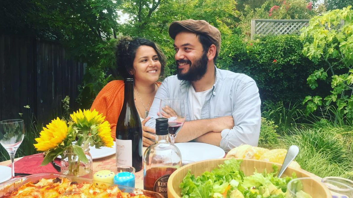 the couple sits outside at a food-laden table with a wine bottle in front of them