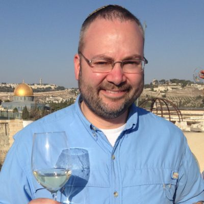 wine columnist stands on Jerusalem rooftop holding a glass of white wine