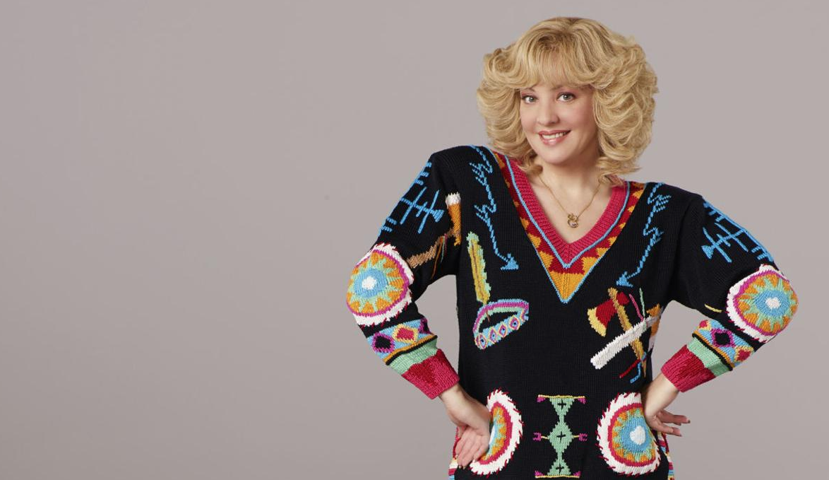 blonde, cheery beverly stands in a loud sweater with arms akimbo