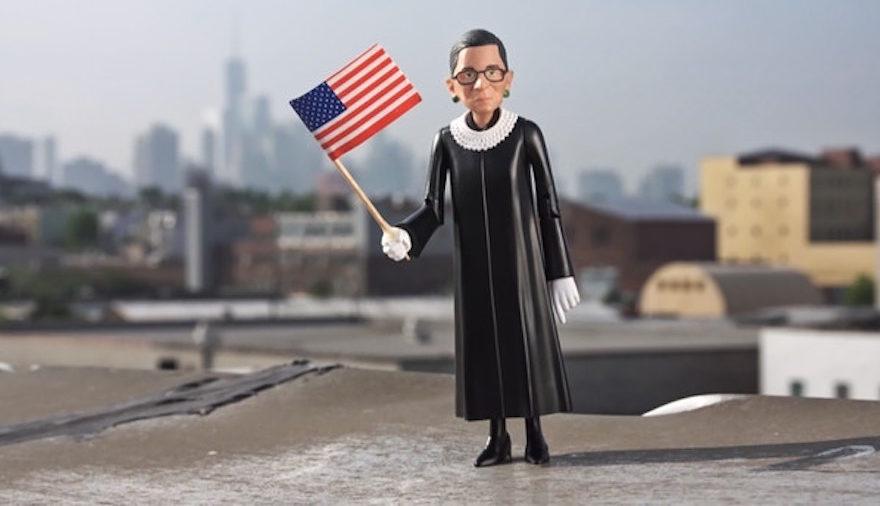 an RBG action figure holding a US flag