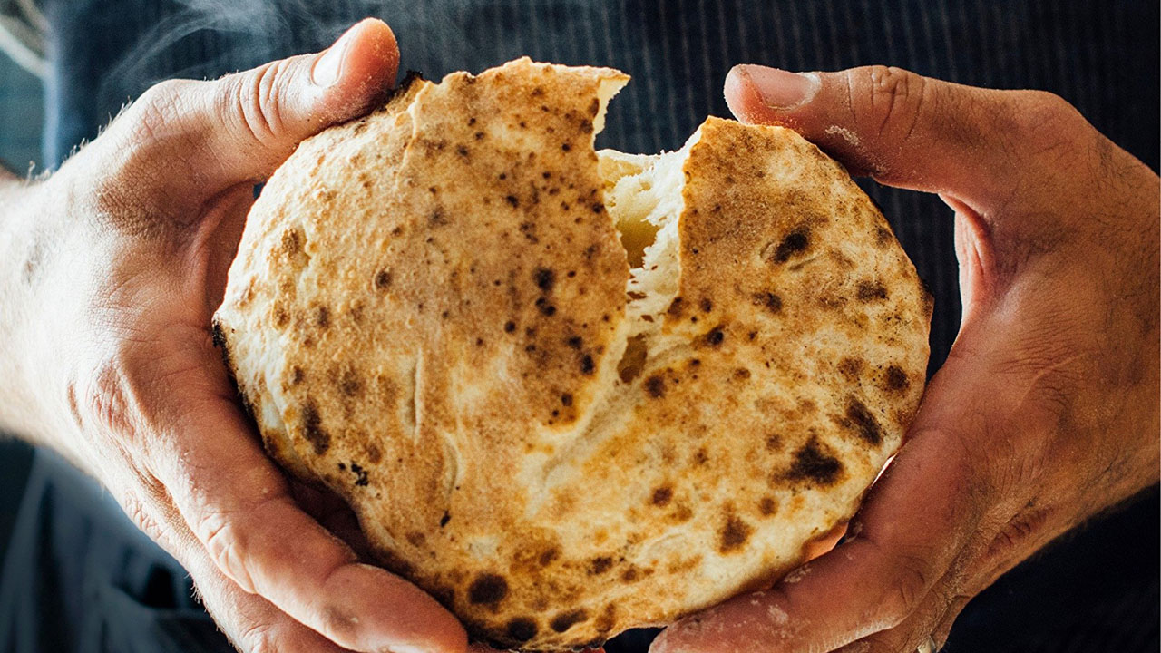 two hands pry into a steaming-hot pita