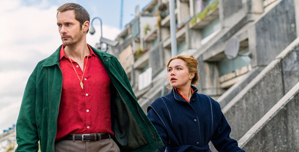 a man in a bright red shirt and green jacket with a stern expression leads a younger woman in a blue coat by the hand