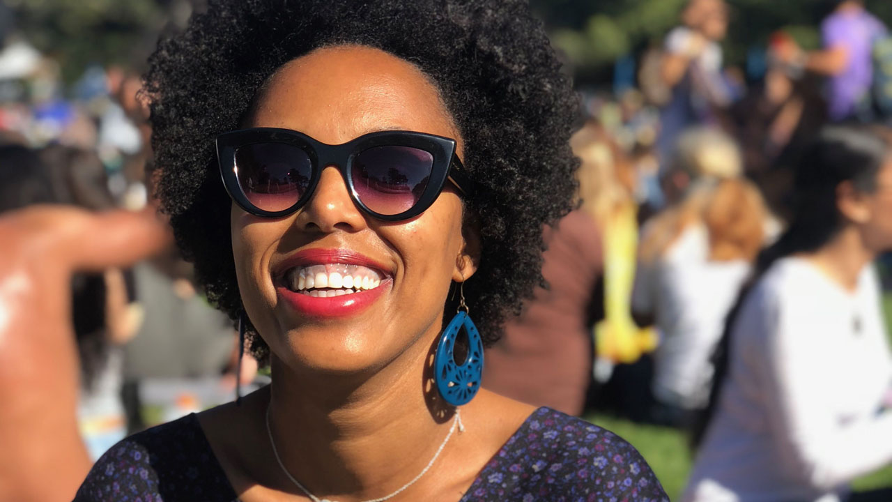 A smiling woman in sunglasses with a big fro