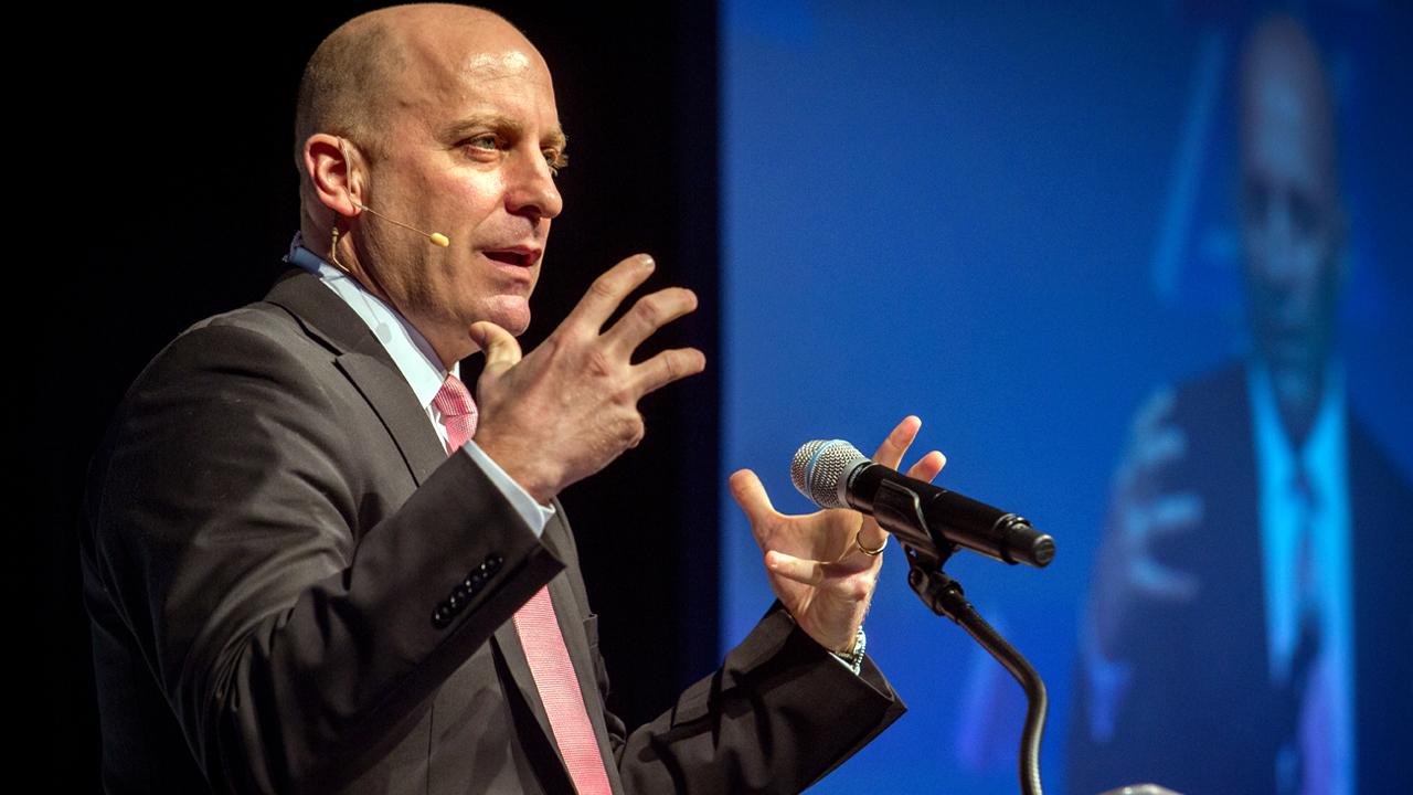 a bald man speaking at a podium