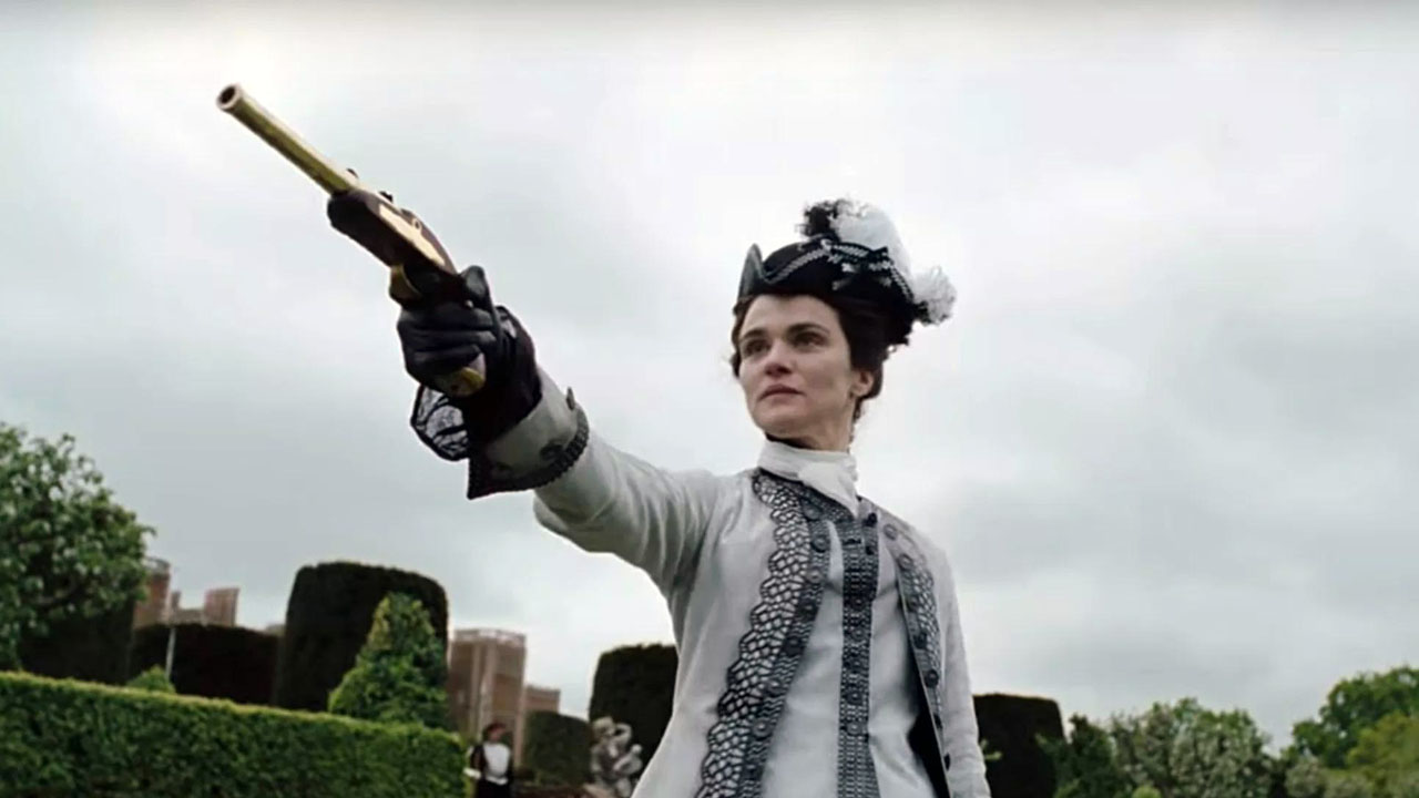 Weisz in an ornate period costume takes aim with a pistol and grave expression