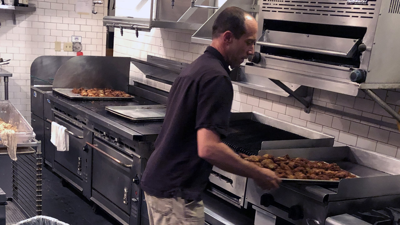 a man in a commercial kitchen holding a large tray of latkes
