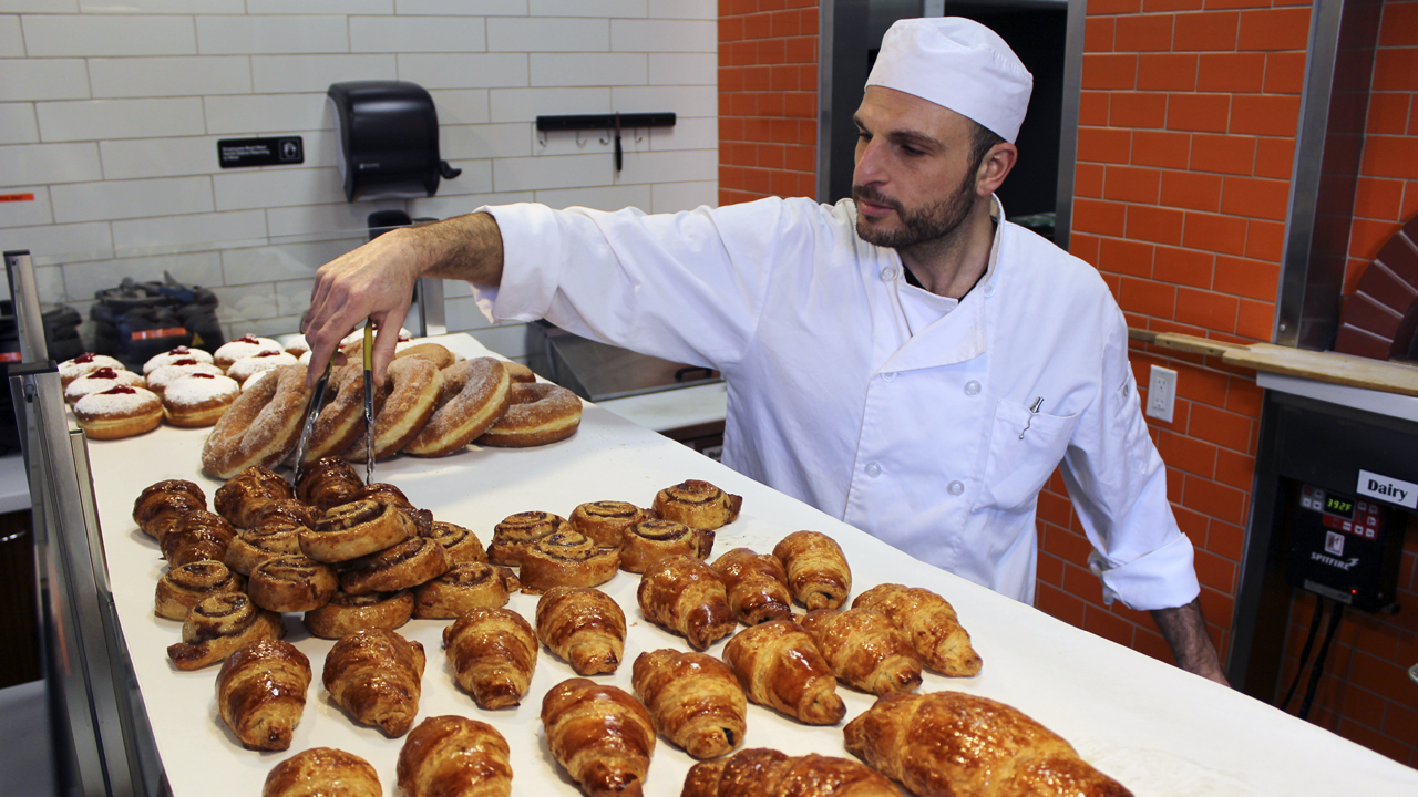a man in chef's whites arranged baked goods in a kitchen