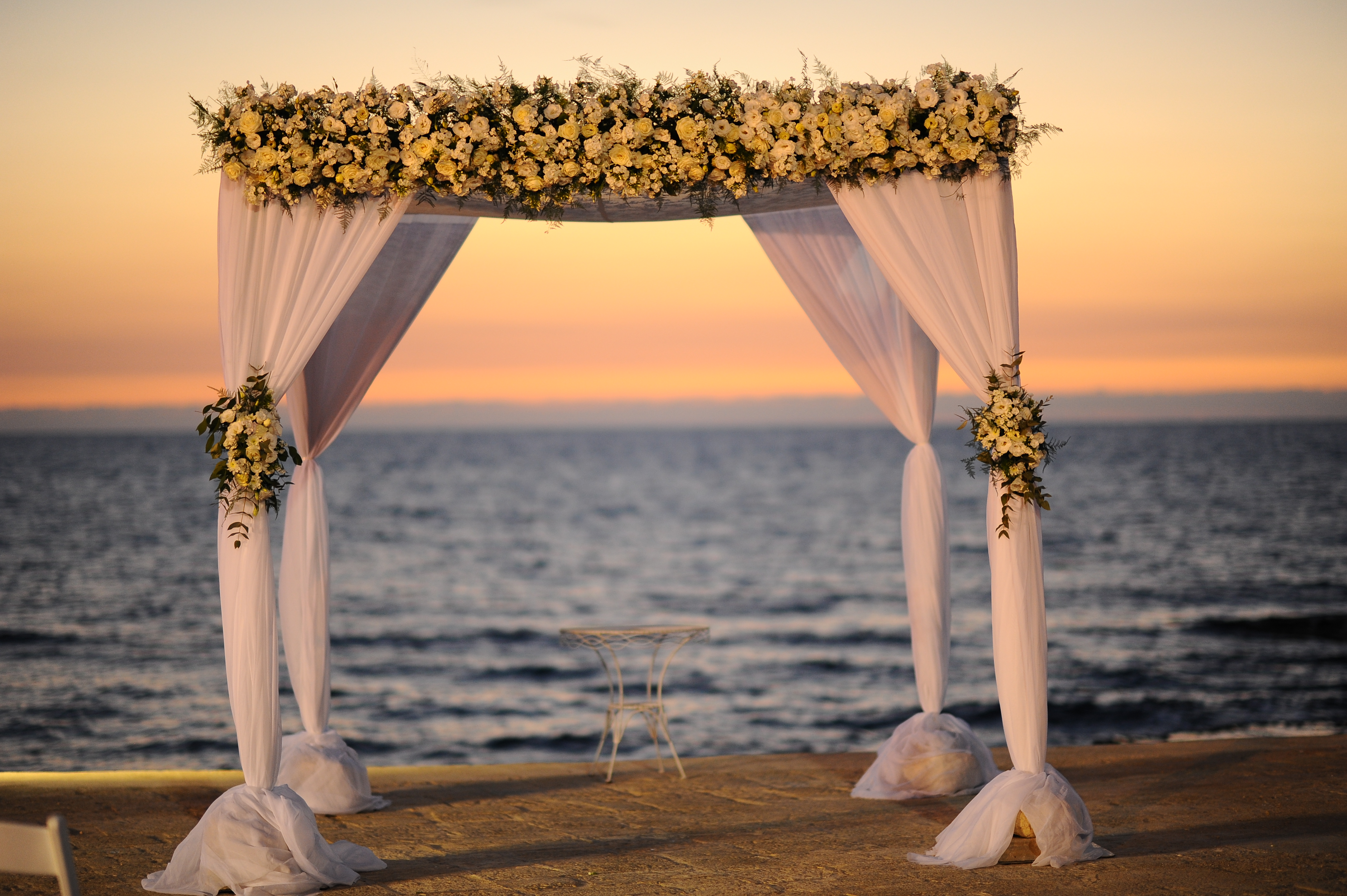 a flowery wedding canopy at sunset by the beach